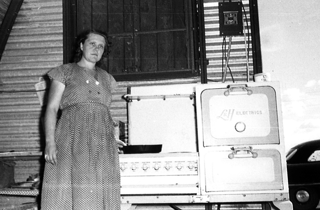 Lady standing in front of her first stove.